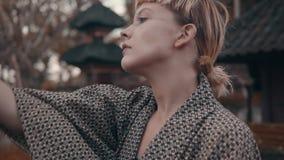 Flicka i kimono med den röda handfanen lager videofilmer