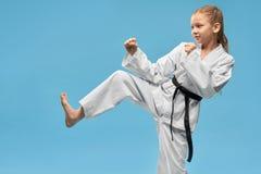 Flicka i kimonot som gör karate på isolerad bakgrund royaltyfri foto