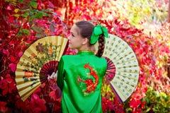 Flicka i kinesisk klänning på en bakgrund av röda sidor Arkivbilder