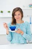 Flicka i köket som äter frukosten Royaltyfria Bilder