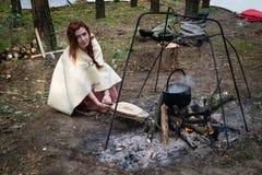 Flicka i kläder av vikingeran nära brandstället royaltyfri bild