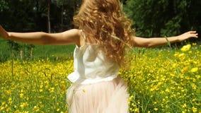 Flicka i klänning med guld- hårspring till och med det gula fältet som trycker på blommor lager videofilmer