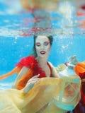 Flicka i klänningen som är undervattens- i simbassängen Fotografering för Bildbyråer