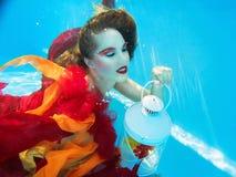 Flicka i klänningen som är undervattens- i simbassängen Royaltyfri Foto