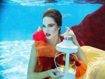 Flicka i klänningen som är undervattens- i simbassängen Royaltyfria Foton