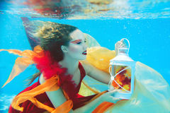 Flicka i klänningen som är undervattens- i simbassängen Arkivfoton