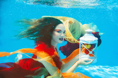 Flicka i klänningen som är undervattens- i simbassängen Royaltyfri Fotografi