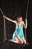 Flicka i klänningplats på böjda ben på swing Arkivbild