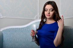 Flicka i klänningsammanträde med ett exponeringsglas av champagne Arkivbilder