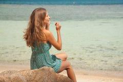 Flicka i klänningsammanträde på en vagga vid havet arkivbilder