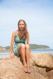Flicka i klänningsammanträde på en vagga vid havet royaltyfria bilder