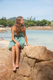 Flicka i klänningsammanträde på en vagga vid havet fotografering för bildbyråer