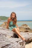 Flicka i klänningsammanträde på en vagga vid havet arkivfoto