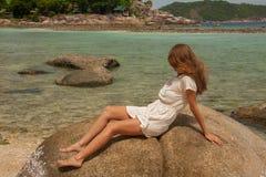 Flicka i klänningsammanträde på en vagga vid havet royaltyfria foton
