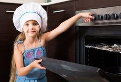 Flicka i kocklock nära ugnen med pizza Arkivfoton