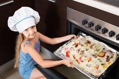 Flicka i kocklock nära ugnen med pizza Arkivbild