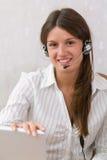 flicka i kontoret med en hörlurar med mikrofon och en bärbar dator Royaltyfri Foto