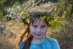 Flicka i kransen av lösa blommor Arkivfoto