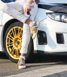Flicka i kulöra gymnastikskoskor och i vit byxa på bakgrund av den vita bilen Flicka på bilbakgrund royaltyfria bilder