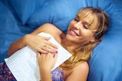 Flicka i läs- förälskelsebokstav för säng från pojkvän Royaltyfri Fotografi
