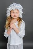 Flicka i lantlig tappning för klänning på en grå bakgrund Royaltyfri Foto