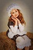 Flicka i lantligt sammanträde för tappningstil på en höstack Royaltyfri Foto