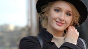 Flicka i leenden för svart hatt som trycker på halscloseupen för blont hår stock video