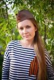 Flicka i likformig av det stora patriotiska kriget Krigaresammanträde på gräset mellan blommor Flicka som bär gröna dräkter av vä Royaltyfria Bilder