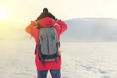 Flicka i ljus kläder som står i en snöig vildmark som rymmer hans huvud Arkivbild