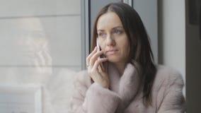 Flicka i ljust lag som talar på en mobiltelefon på fönstret arkivfilmer