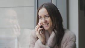 Flicka i ljust lag som talar på en mobiltelefon på fönstret lager videofilmer