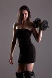 Flicka i lyftande vikter för sexig svart klänning Arkivbilder