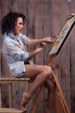 Flicka i målarfärgen med borstar Arkivbild