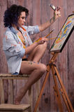 Flicka i målarfärgen med borstar royaltyfri fotografi