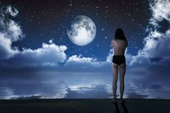 Flicka i månsken Arkivbild