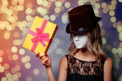 Flicka i maskering för bästa hatt och vitmed gåvaasken fotografering för bildbyråer