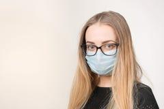Flicka i medicinsk maskering med respiratorn på vit bakgrund arkivfoto