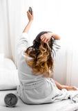 Flicka i morgonen i säng med klockan Arkivbilder