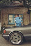 Flicka i ninetiesna som sitter på huven av bilen royaltyfria bilder