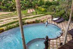Flicka i oändlighetspöl in mot djungel med palmtrees royaltyfria bilder