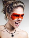 Flicka i orange skrika för lädermaskering Arkivbilder
