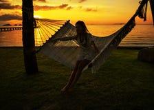 Flicka i palmträd för ett hängmattabesvär som tycker om en tropisk semester fotografering för bildbyråer