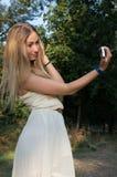 Flicka i parkera med din smartphone Arkivbilder