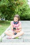 Flicka i parkera med hennes telefon royaltyfri bild