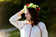Flicka i person som tillhör en etnisk minoritetkläder med kransen av att fira för blommor Royaltyfri Bild