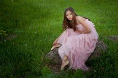 flicka i pointe i ett långt klänningsammanträde på en vagga i th Arkivfoto