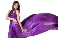 Flicka i purpur klänning för flyg Royaltyfri Foto