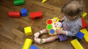 Flicka i purpurfärgade kortslutningar som har gyckel med leksaker på golvet stock video