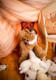 Flicka i pyjamas som spelar med den flotta nallebjörnen på sovrummet Arkivfoto