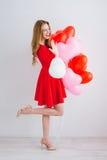 Flicka i röd klänning med ballonger i formen av en hjärta Arkivbild